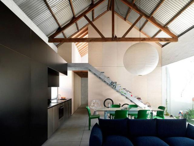 Bộ sofa được đặt quay mặt vào một phần tường để tạo nên vùng chức năng. Thêm bàn trà, ghế nhỏ, những chồng sách được đặt ngay ngắn giúp cho không gian tiếp khách, sinh hoạt chung của gia đình thêm ấm cúng.
