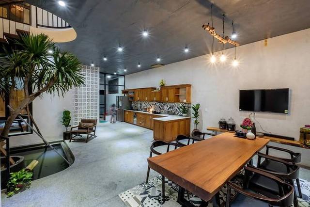 Bước vào nhà là không gian sinh hoạt chung với phòng bếp - ăn ngăn nắp, sạch sẽ. Kiến trúc sư cho hay phần trần nhà làm sàn rỗng ubot, không dầm, để thô, sơn lên lớp màu ghi bảo vệ, tạo ra nét đẹp thô mộc. Tủ, kệ bếp gỗ tạo cảm giác ấm cúng cho không gian nấu nướng.