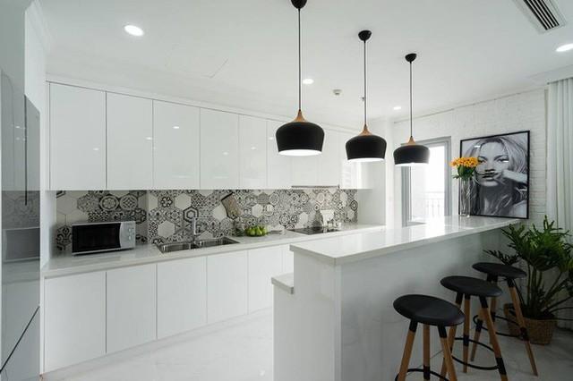 Tường bếp ốp gạch lục giác Tây Ban Nha độc đáo. Tủ bếp kiêm quầy bar cũng là một thiết kế thông minh.