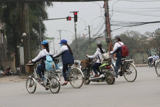 Học sinh đi xe máy, xe đạp điện không đội mũ bảo hiểm là hình ảnh khá phổ biến trên đường phố Hà Nội. Ảnh: Chí Cường