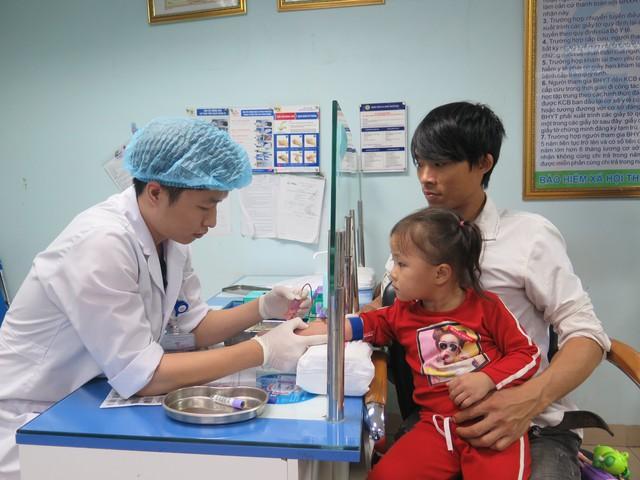 Các bác sỹ đang lấy máu xét nghiệm cho hai bố con