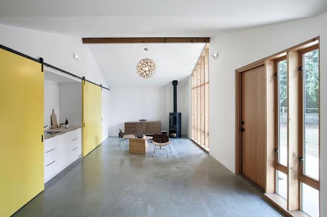 Toàn bộ nội thất sử dụng trong ngôi nhà có màu nâu sáng. Tường và sàn bê tông sơn trắng làm nổi bật các viền gỗ của cửa chính và cửa sổ.