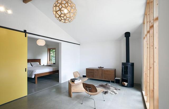 Cửa trượt màu vàng phân chia không gian phòng khách và phòng ngủ. Chỉ mất vài bước chân, cặp vợ chồng có thể di chuyển từ khu sinh hoạt chính sang nơi nghỉ ngơi.