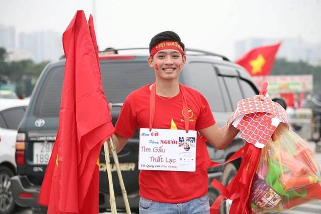 Chàng trai thu hút người mua cờ, băng-rôn bằng cách độc đáo.