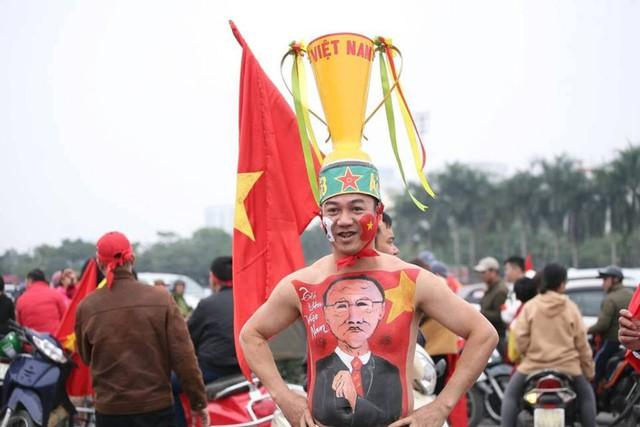 CĐV đội trên đầu chiếc cúp vàng vô địch trước trận đấu và vẽ sơn lên mình hình ảnh lá cờ Tổ quốc cùng thầy Park.