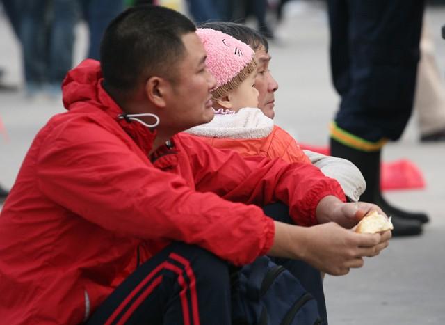 Một người đàn ông đang cố ăn chiếc bánh mì lót dạ.