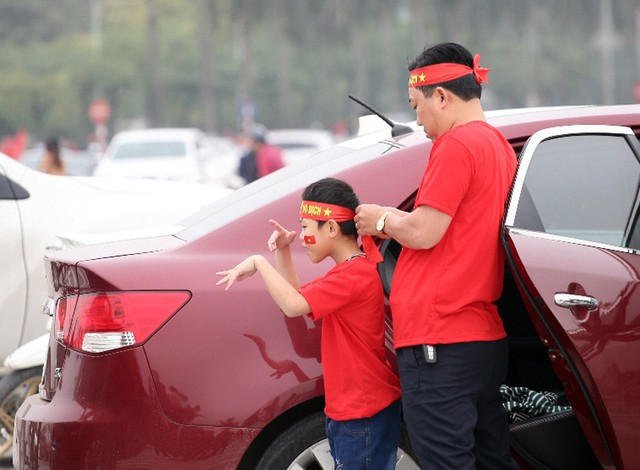 Cha mẹ chuẩn bị áo đỏ, cờ đỏ sao vàng, băng-rôn để hòa mình vào dòng người.