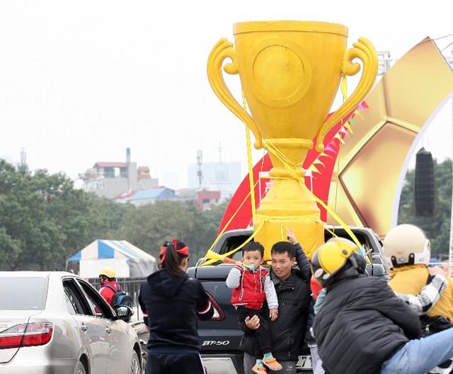 Một chiếc cúp vô địch cỡ lớn được chủ nhân chiếc xe bán tải chở quanh sân.
