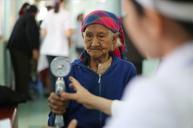Một cụ bà ở Đắk Nông được thăm, khám chữa bệnh miễn phí. Ảnh: Lao động