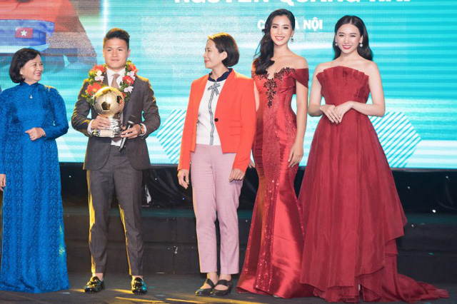 Quang Hải lên sân khấu nhận cúp Quả bóng vàng 2018. Với chiều cao khiêm tốn, anh nhỏ bé khi đứng gần hai người đẹp Tiểu Vy và Hari Won.