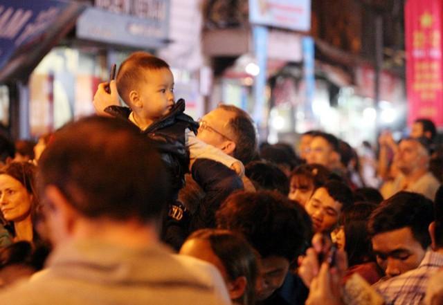 Một bé trai đang ngơ ngác tự hỏi vì sao lại bị lạc vào dòng người đông đến như thế.