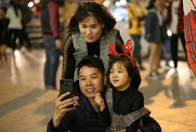 Một gia đình trẻ cho con gái đi chơi, chụp ảnh và hưởng không khí Giáng sinh trong tiết trời se lạnh.