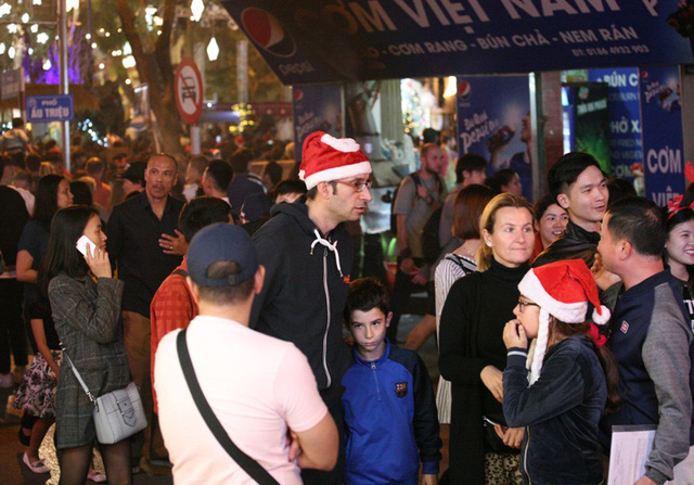 Nhiều du khách ngoại quốc cũng hòa mình vào dòng người chào đón Giáng sinh.