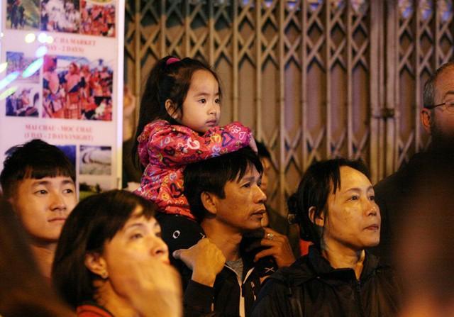 Bé gái được bố cõng sát khu vực tường nhà dân để xem các tiết mục văn nghệ.