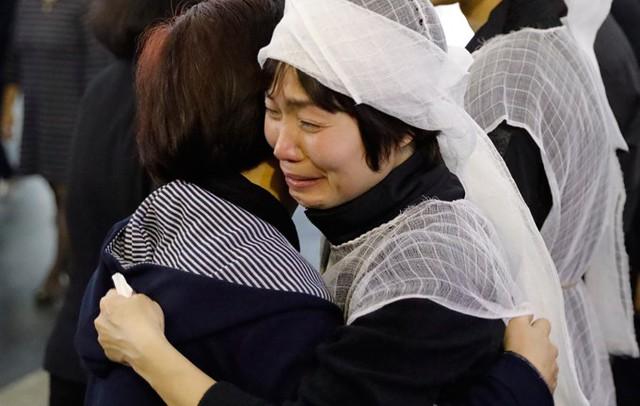 Trong tang lễ, những cái ôm của bạn bè không làm vơi bớt đi nỗi đau mất chồng của chị Mai.