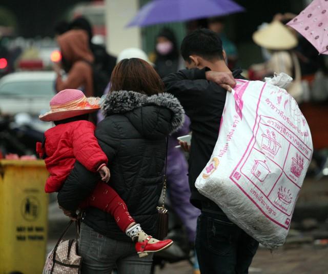 Hình ảnh cha mẹ bế trẻ nhỏ trên tay thường thấy tại các bến xe dịp này. Tuy nhiên, do thời tiết Hà Nội mưa và rét nên ai cũng thấy thương.