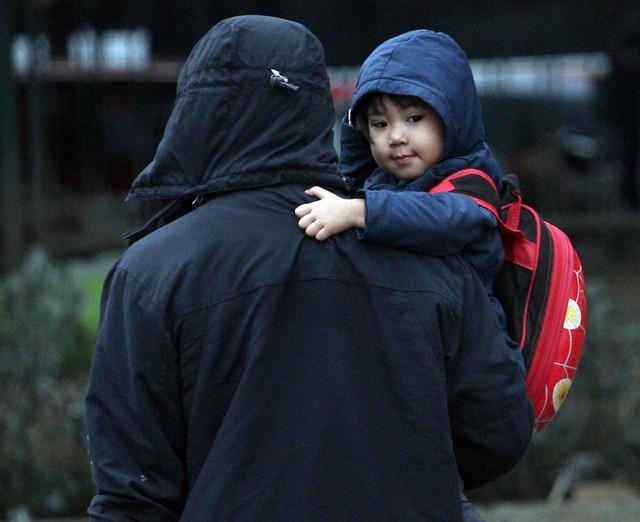 Một ông bố vừa đón con đi học về đã nhanh chân đến bến xe chờ vợ để cả nhà cùng lên xe về Phú Thọ.