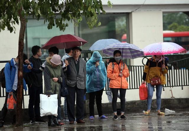 Đối với những người dân di chuyển về các huyện ngoại thành Hà Nội phải chờ xe buýt dưới mưa.