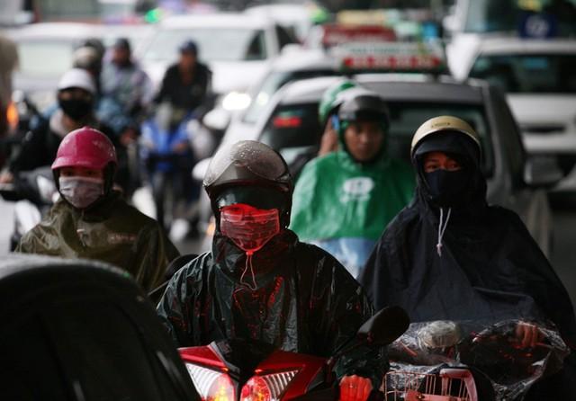 Người phụ nữ dù đã mặc áo mưa nhưng vẫn bị ướt dưới thời tiết khắc nghiệt.