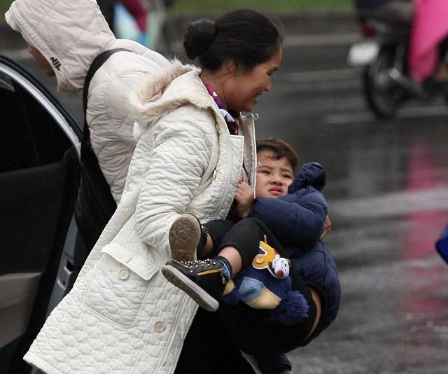 Hoặc cậu bé vừa cùng bà bước từ trên taxi xuống chưa quen với thời tiết mưa lạnh nên tỏ vẻ khó chịu.