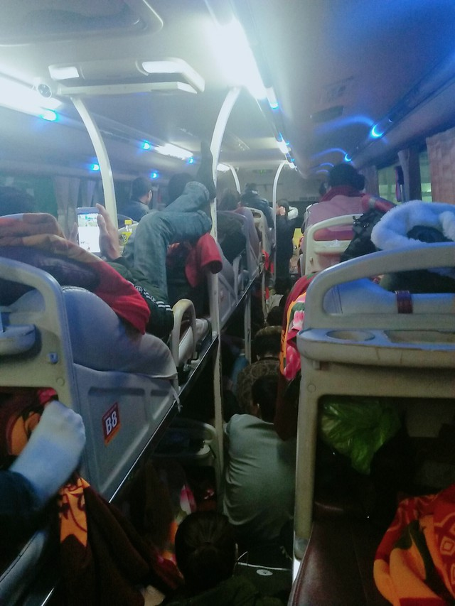 Một xe khách giường nằm hết chỗ đã xếp hành khách ngồi sát nhau giữa lối đi.