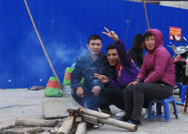 Trên đường Phạm Văn Đồng, nhiều người dân tranh thủ sưởi ấm cơ thể trước khi bắt đầu công việc mới của mình.