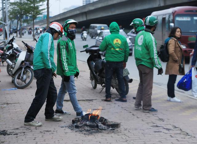 Trong khi đó, một nhóm thanh niên chạy xe ôm công nghệ quanh BX Mỹ Đình đã nhóm lửa cùng sưởi ấm cơ thể trong lúc chờ khách.