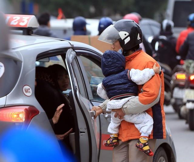Một người đàn ông ôm con mình để về quê bằng taxi sau thời gian dài chờ xe khách không được.
