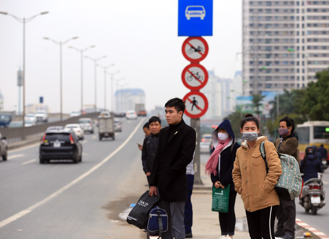 Tại lối vào đường cao tốc trên cao, nhiều thanh niên đứng chờ xe khách dù đây là khu vực cấm.