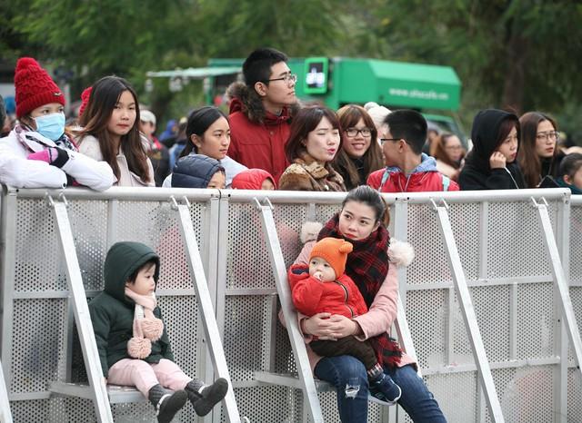 Một bà mẹ đưa trẻ nhỏ ngồi nép mình sau hàng rào để tránh những cơn gió lùa vào người.