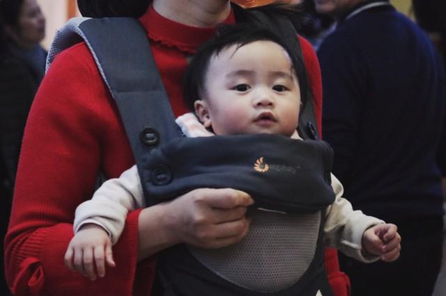 Một em bé được mẹ địu đi chơi tỏ ra rất phấn khích.