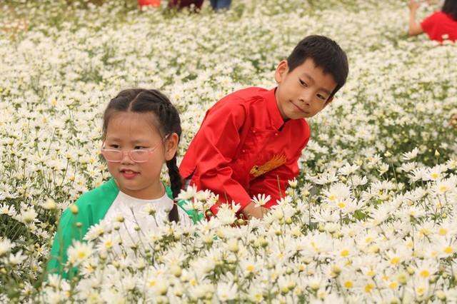 Hai bạn nhỏ được bố mẹ cho đến chụp hình ở vườn hoa.