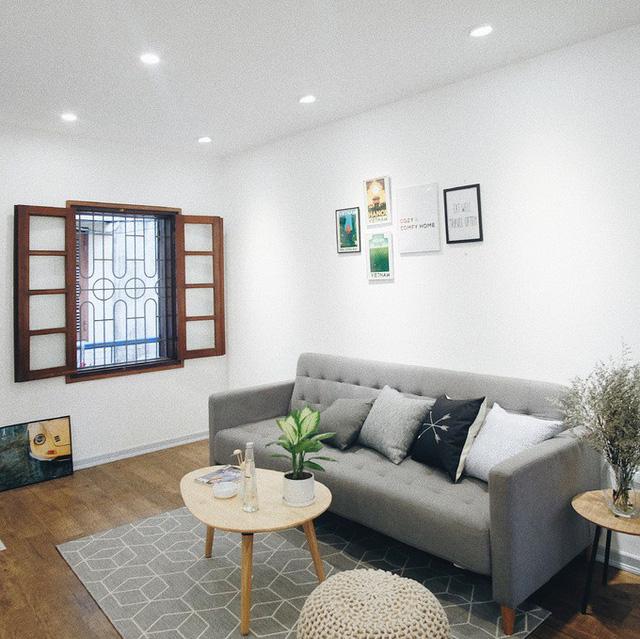 Phòng khách của ngôi nhà sáng đẹp như nhà mẫu sau khi được sơn trắng đồng bộ, làm lại trần, sàn gỗ, kết hợp với đồ nội thất xinh xắn.