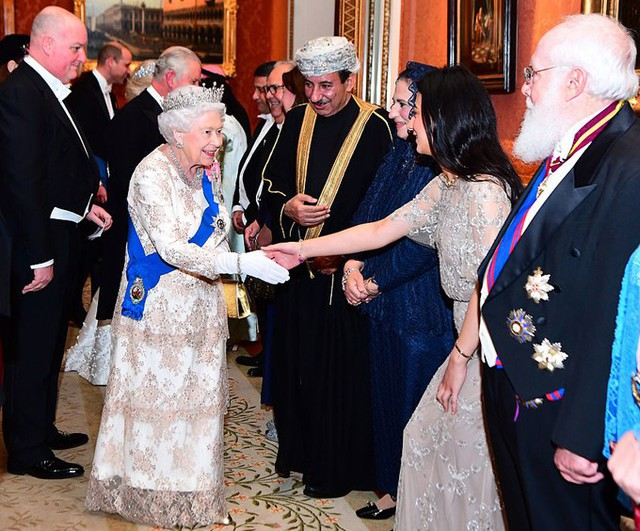 Trong khi đó, Nữ hoàng cũng mặc một chiếc váy ren cầu kỳ và đeo vương miện để tiếp đón 1.000 khách mời, bao gồm các đại sứ và cao ủy tại Anh.