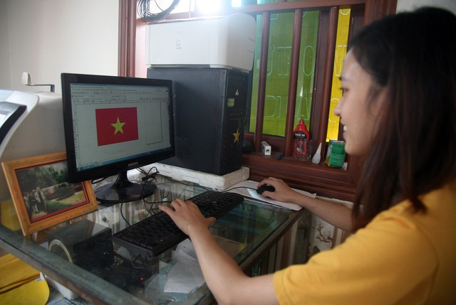 Vân Anh – con gái cả của gia đình chị Nhung đảm nhiệm việc vận hành máy cắt cờ, băng-rôn, miếng dán và hình ngôi sao vàng.