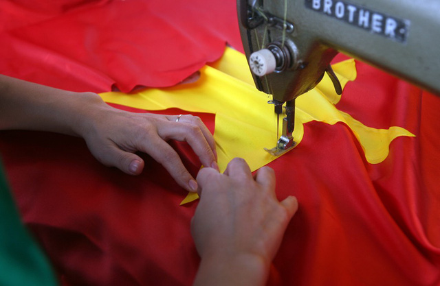 Sau khi máy cắt thực hiện định hình lá cờ, thợ may sẽ thực hiện công đoạn may ngôi sao vàng vào giữa.