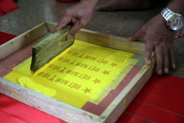 """Những tấm băng-rôn sau khi lấy ra từ máy cắt sẽ được dập khuôn in chữ """"Việt Nam vô địch""""."""