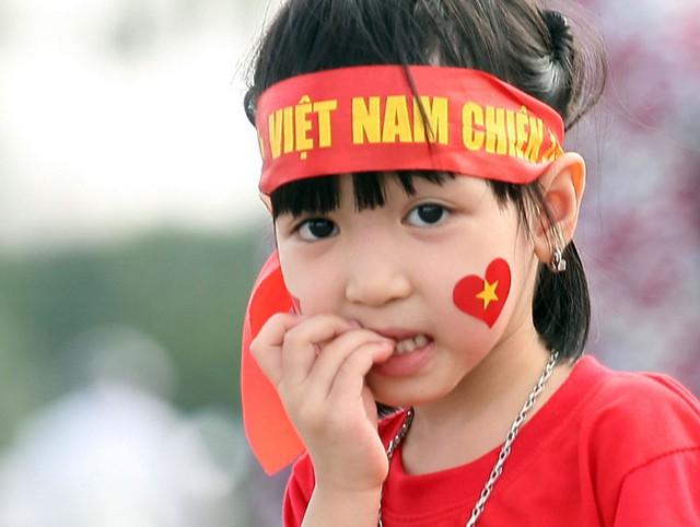 Một bé gái được cha mẹ cho khoác lên mình áo in hình cờ đỏ sao vàng tỏ ra ngạc nhiên trước dòng người đông đúc.