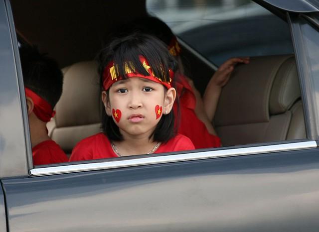 Bé gái trên xe ô tô quan sát dòng người đổ về sân ngày càng đông đúc.