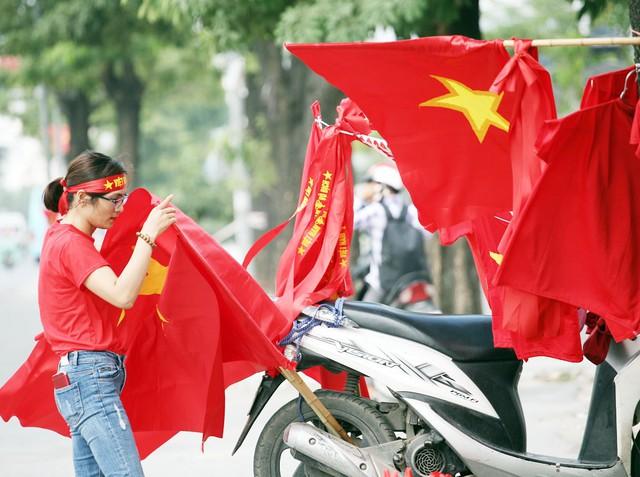 Dọc đường Lê Quang Đạo nhiều người bán cờ, băng-rôn phục vụ người hâm mộ.