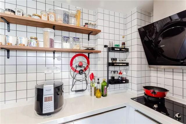 Vì không nấu ăn thường xuyên, cũng không hoàn toàn dùng đồ takeaway, chủ nhà sử dụng tông màu sáng cho nhà bếp, gạch ốp tường màu đen, vách ngăn bằng gỗ để đặt các hộp thức ăn lên những phân vùng khác nhau. Hầu hết là những loại gia vị, đồ dùng nhà bếp đều được lưu trữ gọn ghẽ, đơn giản mà cực đẹp.