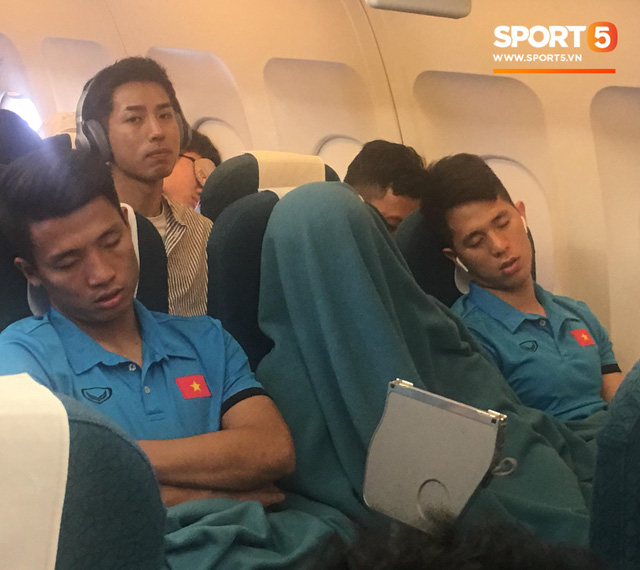 Duy Mạnh trùm chăn kín đầu để ngủ trên chuyến bay tới Malaysia. Ảnh: Hiếu Lương
