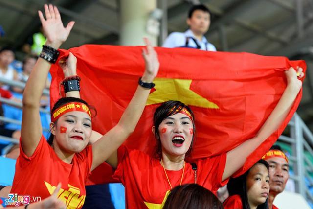 Đỗ Thị Hương (phải), sinh viên người Việt Nam đang học tại Singapore rủ bạn (bên trái) là người Philippines đi cổ vũ bóng đá. Ảnh: Hoàng Hà.