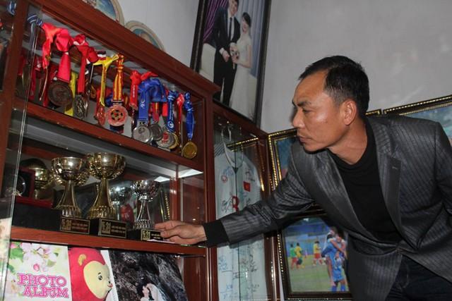 Ông Nguyễn Đức Đông bên những thành tích của con trai út. Ảnh: Đ.Tùy