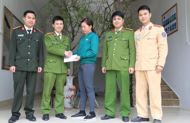 Công an huyện Tiên Yên bàn giao số tiền lừa đảo của đối tượng cho chị Hạnh. Ảnh: X.Thao
