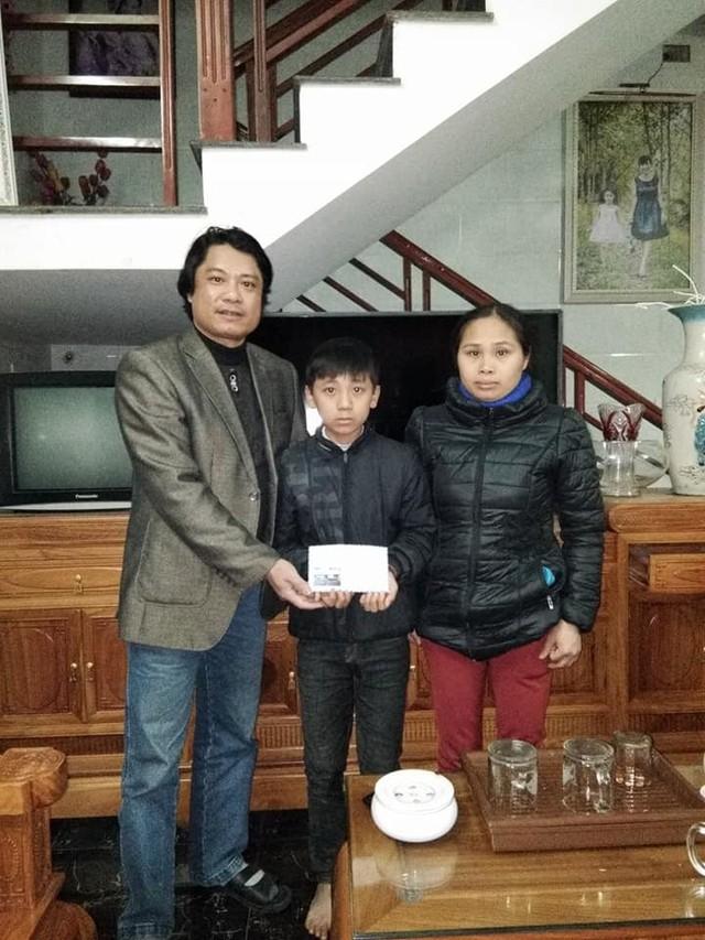 Thầy Vũ Trọng Hoài thay mặt một số nhà hảo tâm trao tặng khoản tiền nhỏ cho mẹ con cậu bé Trần Thế Bảo. Ảnh. TH.