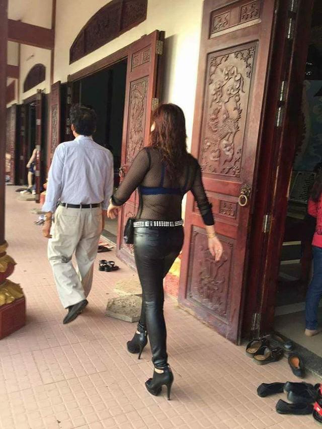 Người phụ nữ ăn mặc sành điệu, quần da, áo lưới khi đi chùa.