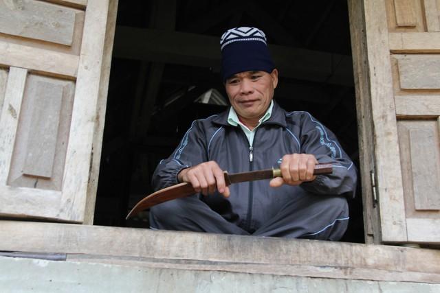 Ông Hiển bên cạnh chiếc dao đi rừng từng gắn bó với ông thời còn hành nghề thầy cúng. Ảnh: PV