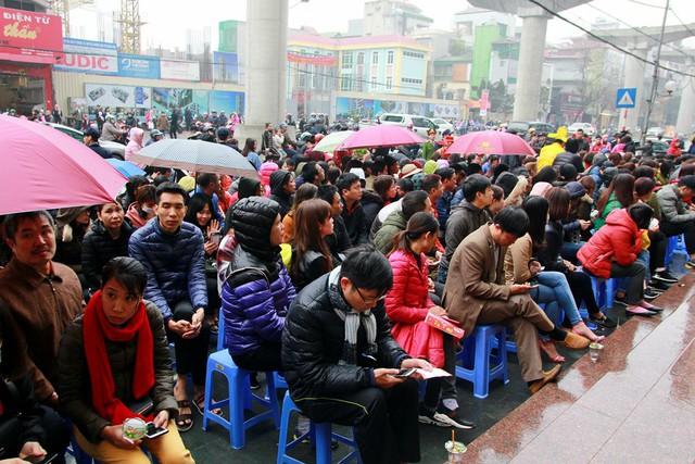 Tại Cừa hàng Bảo Tín Minh Châu (319 Cầu Giấy, Hà Nội) hàng dài người xếp hàng dưới mưa chờ mua vàng cầu may.