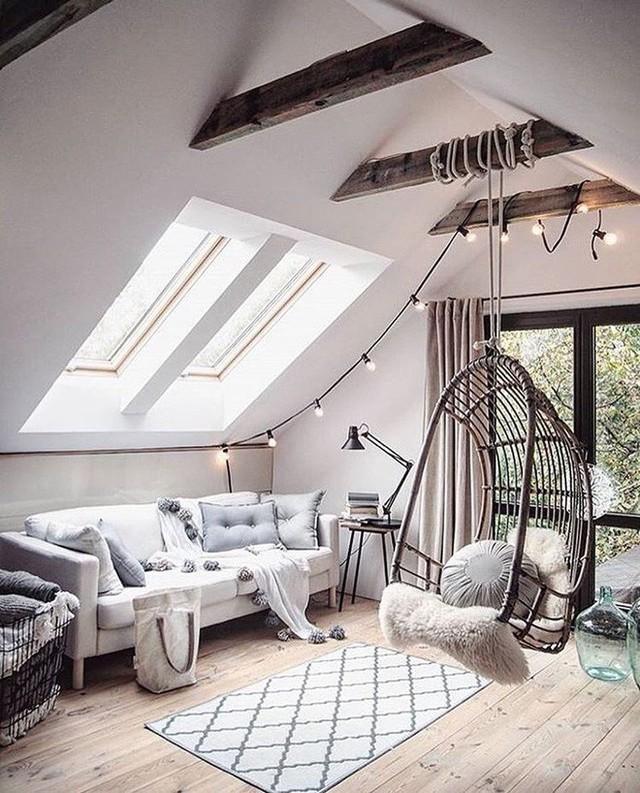 Trần nhà nổi bật với dầm gỗ và đèn chiếu sáng và ghế mây treo.
